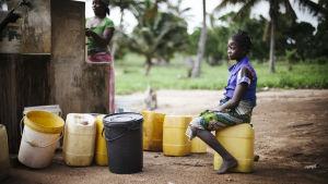 En flicka sitter och vilar sig på en vattendunk av plast invid en brunn.