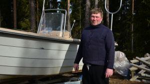 Tom Blom brevid en av sina fiskebåtar