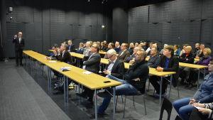 Ossi Repo förklarar kommunutredning för åhörarna i Vasa stadsbibliotek.