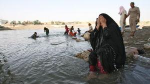 Kvinna svalkar sig med vatten vid floden Tigris i Bagdad