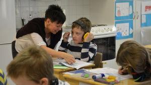 Lärare hjälper elev i undervisningen