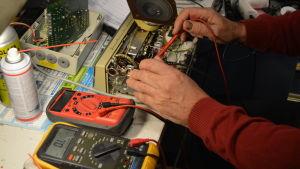 Reparatören mäter komponenter i en gammal radio