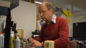Elektronikreparatör Rabbe Högström mäter komponenter för att hitta felet
