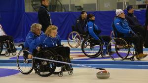 Sari Karjalainen kastar medan Vesa Leppänen håller i rullstolen.