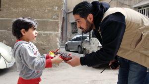 Biståndsarbetare hjälper palestinsk flykting på läger i Syrien.