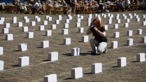 Medlem i Amnesty International placerar ut symboliska gravstenar i Amsterdam till minne av de hundratals migranter som har drunknat i Medelhavet under färden till Europa.