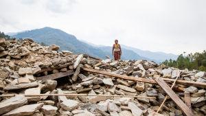 kvinna står på ruinerna efter jordbävning i Nepal