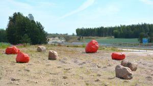Fyra röda stenar intill motorvägen i Pyttis.