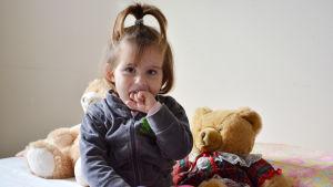 Tre år gammal flicka sitter på en säng med några nallar.