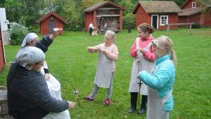 Elever från Merituulen koulu spinner garn på tidsresa vid Gammelgården i Ingå