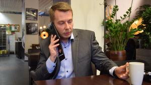 Barnombudsman Tuomas Kurttila på kafé, ringer med mobiltelefon