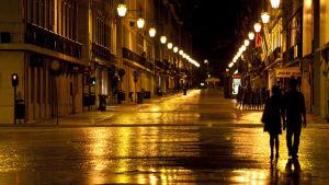 pariskunta kävellee kaupungissa yöllä