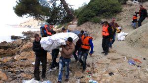 Pakolaiset kantavat rannalla kumivenettä