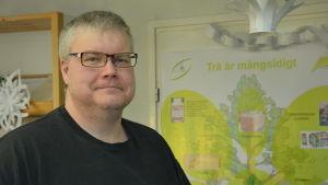Stefan Willför står framför en planch om trädets mångsidighet.
