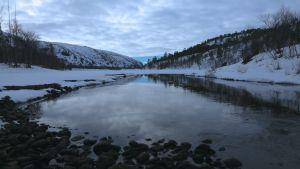Leveähkö seesteisesti kulkeva virta lumisessa maisemassa. Taustalla kohoavat jyrkänteet. Taivaalla on pilvikatto.