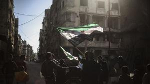 Syrier protesterade på fredagen mot misstänkta brott mot eldupphöret i stadsdelen Douma i Damaskus utkanter.