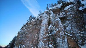 Korkea kevyesti lumen puuteroima punertavankeltainen kallio nousee jyrkästi kohtisuoraan ylös. Kallion päällä näkyy kaukana mäntyjä. Taivas on sininen, sitä halkoo leveähkö harsomainen pilvivana.