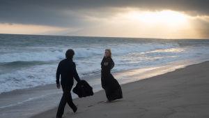 Christian Bale och Cate Blanchett på en strand i solnedgången.