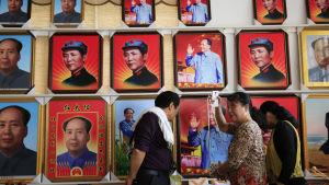 Besökare tittar på souvenirer framför en vägg med porträtt av Mao Zedong i Shaoshan i Hunanprovinsen i Kina. Shaoshan var Maos hemstad.