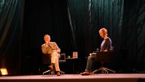Två personer sitter på en scen o samtalar