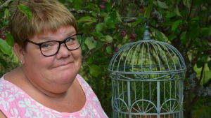 Susanne Gustafsson står nära en fågelbur med växtlighet.