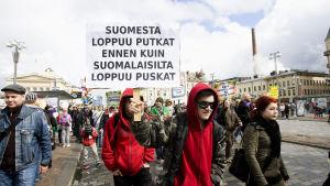 """Nuoria osoittamassa mieltään kannabiksen laillistamisen puolesta Hämeenkadulla Tampereella. Nuoria mielenosoituksessa. Kyltti, jossa teksti """"Suomesta loppuu putkat ennenkuin suomalaisilta loppuu puskat""""."""