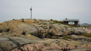 Adrian Perera ligger på klipporna på Klovharun och läser.