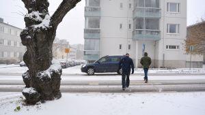 Två män går på övergångsstället på Alexandersgatan i Borgå. Till vänster en tjock, gammal trädstam.