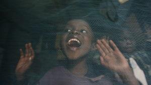 Glatt barn bakom ett myggnät.