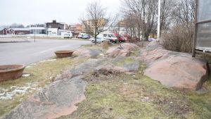 En plats med stenar och gräs och träd utanför HSF i Hangö där det ska finnas moduler med toaletter och dusch för gästbåtafolket.