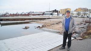 Kalle Niemi står vid gästhamnsbryggan i Hangös Östra hamn. I bakgrunden syns HSF och de röda magasinen.