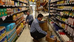 Två män radar in produkter i butikshyllor.