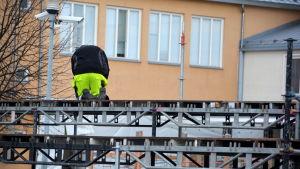 Person som hjälpte ta ner läktarna på bandyplanen i Borgå efter finalmatchen.