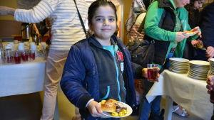Pojke med saft och kakor på ett fat.
