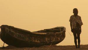 Poika kävelee rannalla Beninissä.