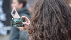 En kvinna med långt mörkt hår tar en bild med en mobiltelefon.