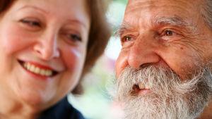 Närbild av en kvinna och en man. Mannen har grått skägg och ler.