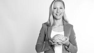Hjärnforskaren Mona Moisala med en modell av en hjärna i handen.