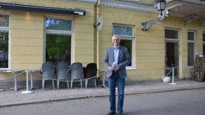Tony Jäntti står vid Bassihuset i Åbo. Balkong och utemöbler bakom honom