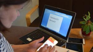 Silja skriver på mobilen framför datorn.