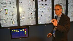 Ulf Lindén håller upp en analog brytare framför en pekskärm i Lovisa kärnkraftverks simulator.