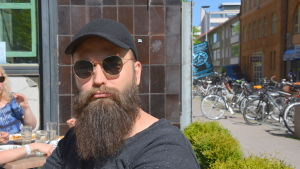 Mikko Manninen is sitting outside and wearing round sunglasses and a black cap. He has a long beard.