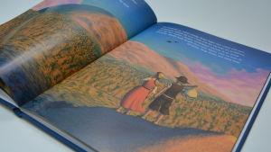 boken björken och stjärnan ligger uppslagen på en bordsyta. På bilden ser man två barn som blickar ut över ett väldigt bergslandskap.