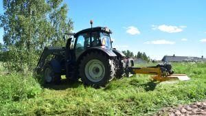Traktor röjer ner gräset vid åstranden i Sjundeå