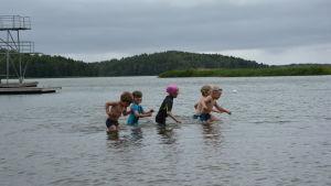 Barnen i simskolan simmar i vattnet.
