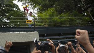 Oppositionsledaren Leopoldo López håller i Venezuelas flagga och hälsar på sina anhängare från en bro i Caracas, Venezuela den 8 juli 2017.
