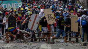 Demonstranter med skyltar fyller en gata i Venezuelas huvudstad Caracas, den 22 juli 2017.
