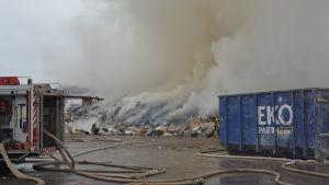 Brandbil och brandmän släcker eld vid en soptipp.