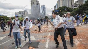 Demonstranter flyr undan säkerhetsstyrkor i centrum av Caracas 30.7.2017.