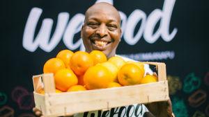 Före detta löparen Wilson Kirwa håller i en trälåda med apelsiner i. I bakgrunder står det Wefood.